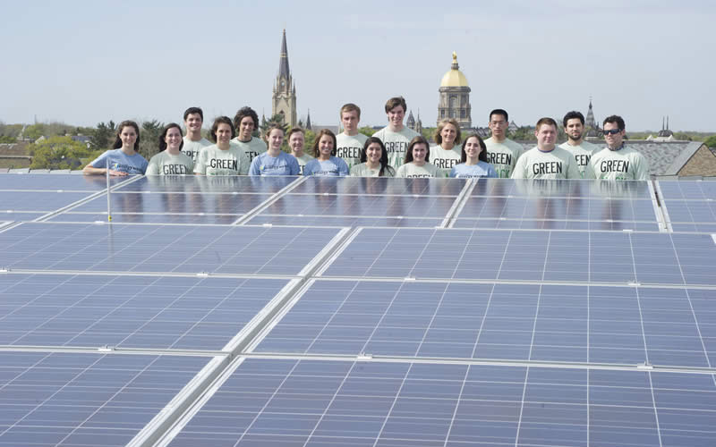 Students behind a solar panel array