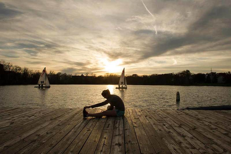 A woman does yoga during sunset at a lake as boats sail in the background.