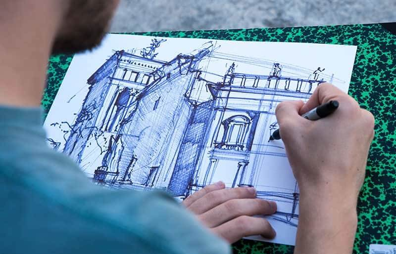 A close up shot of a student sketching an architectural building.